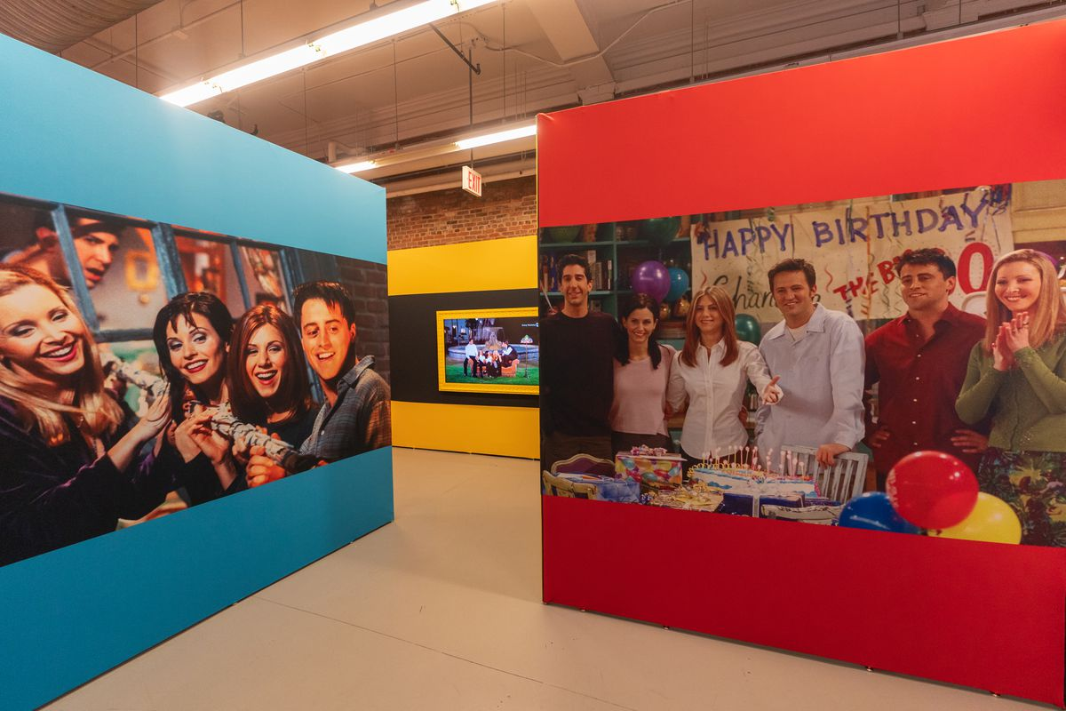 Two large photos of the cast from the show 'Friends' line walls of a show exhibit