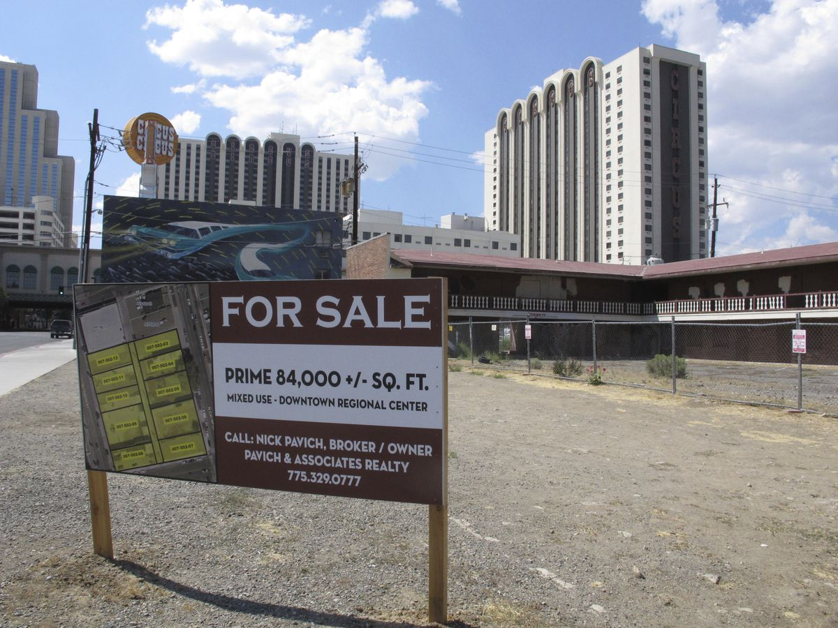 """A """"for sale"""" sign in the foreground, with high-rises in the background."""
