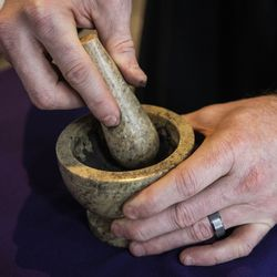 Pastor Ben Adams uses a mortar and pestle to prepare ashes for the imposition at Holy Trinity Lutheran Church in the South Loop on Ash Wednesday, Feb. 17, 2021.