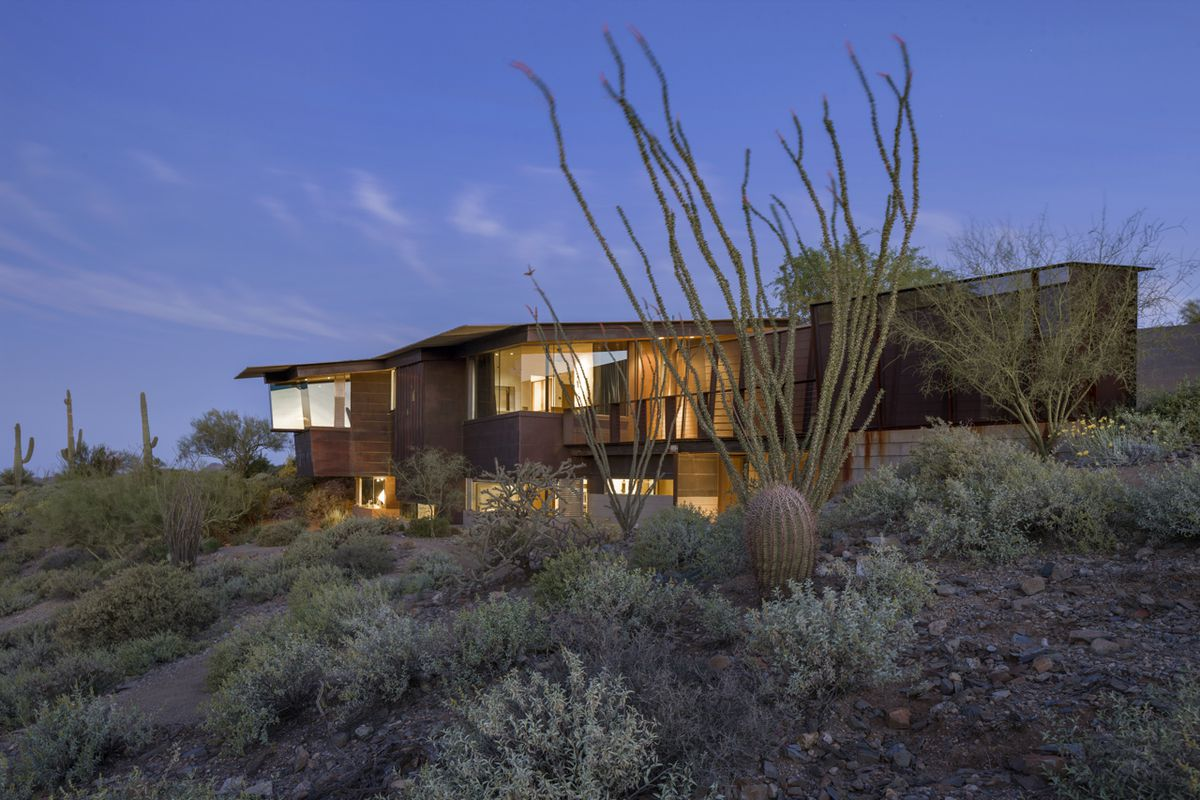 A geometric modern home with offset roof and glazed walls sits on desert site studded with cacti.