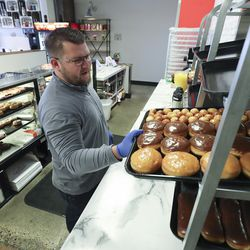 Cowboy Donuts owner Derek Johnson looks over donuts at his shop in Spanish Fork on Tuesday, April 14, 2020. Podium has developed and released, free of charge, an interface that allows food businesses to operate takeout services entirely on a text chain from ordering to payment.
