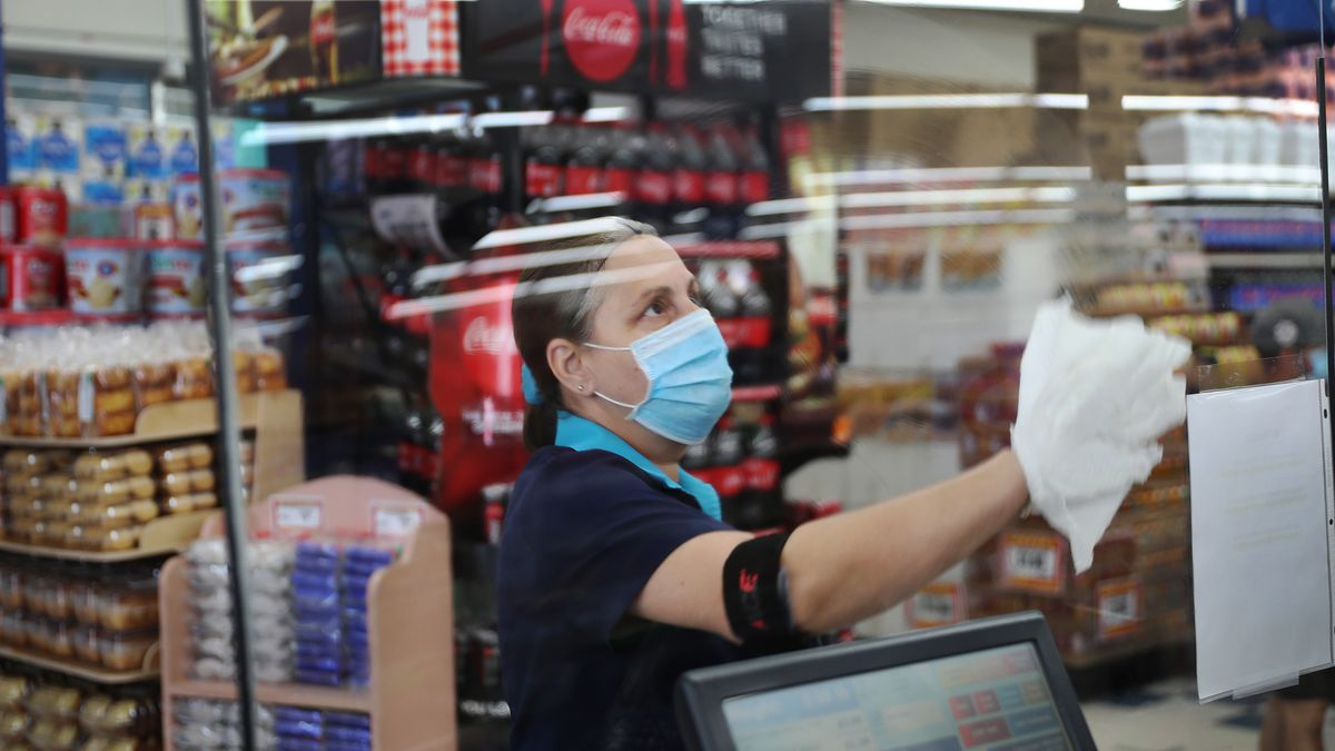 Woman wearing a mask and gloves uses towel to wipe down screen.