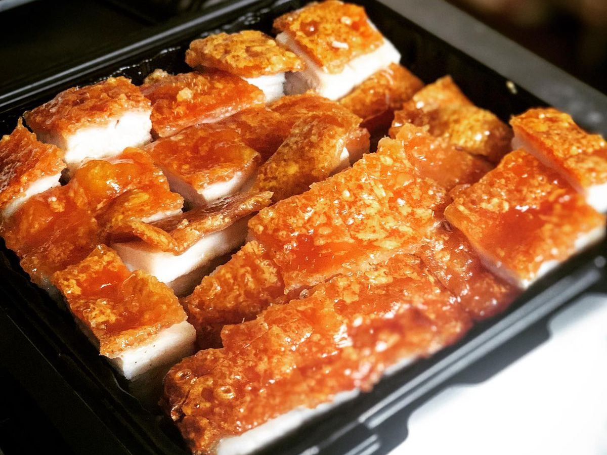 A takeout container packed with chopped roast pork with very crispy skin on top