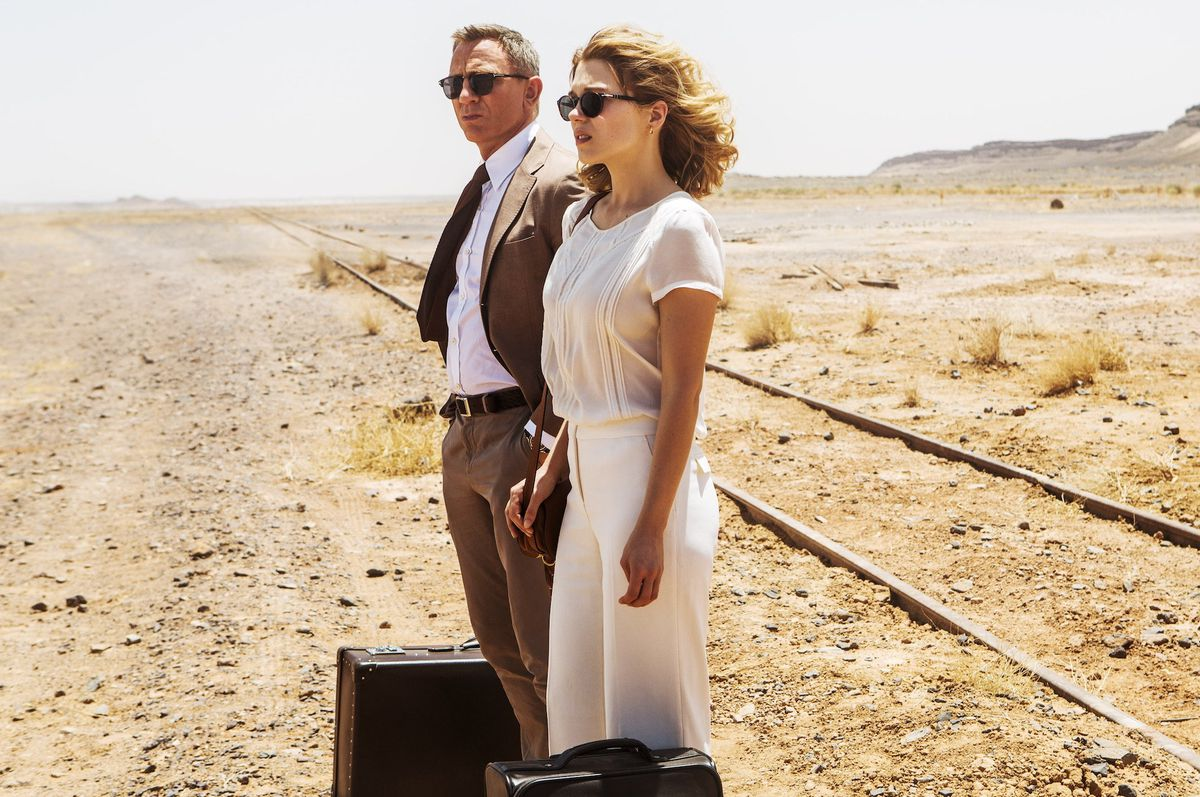 Bond and Madeline Swann stand in a desert with their luggage waiting for a train