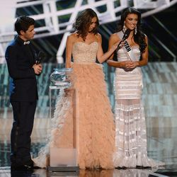 From left, recording artist and host Nick Jonas and television personality and host Giuliana Rancic look on as Miss Utah Marissa Powell answers a question from the judges during the interview portion of the Miss USA 2013 Pageant Sunday, June 16, 2013, in Las Vegas.