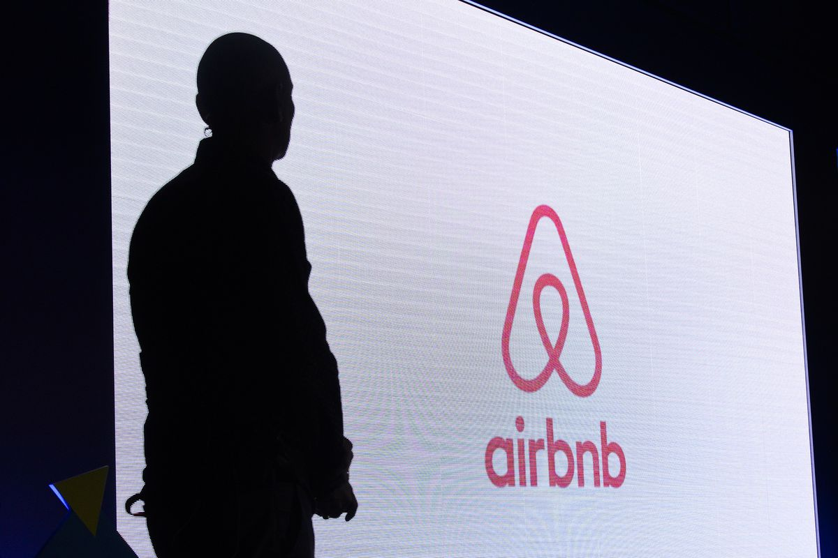 A silhouette in front of a screen with a white and red Airbnb logo.