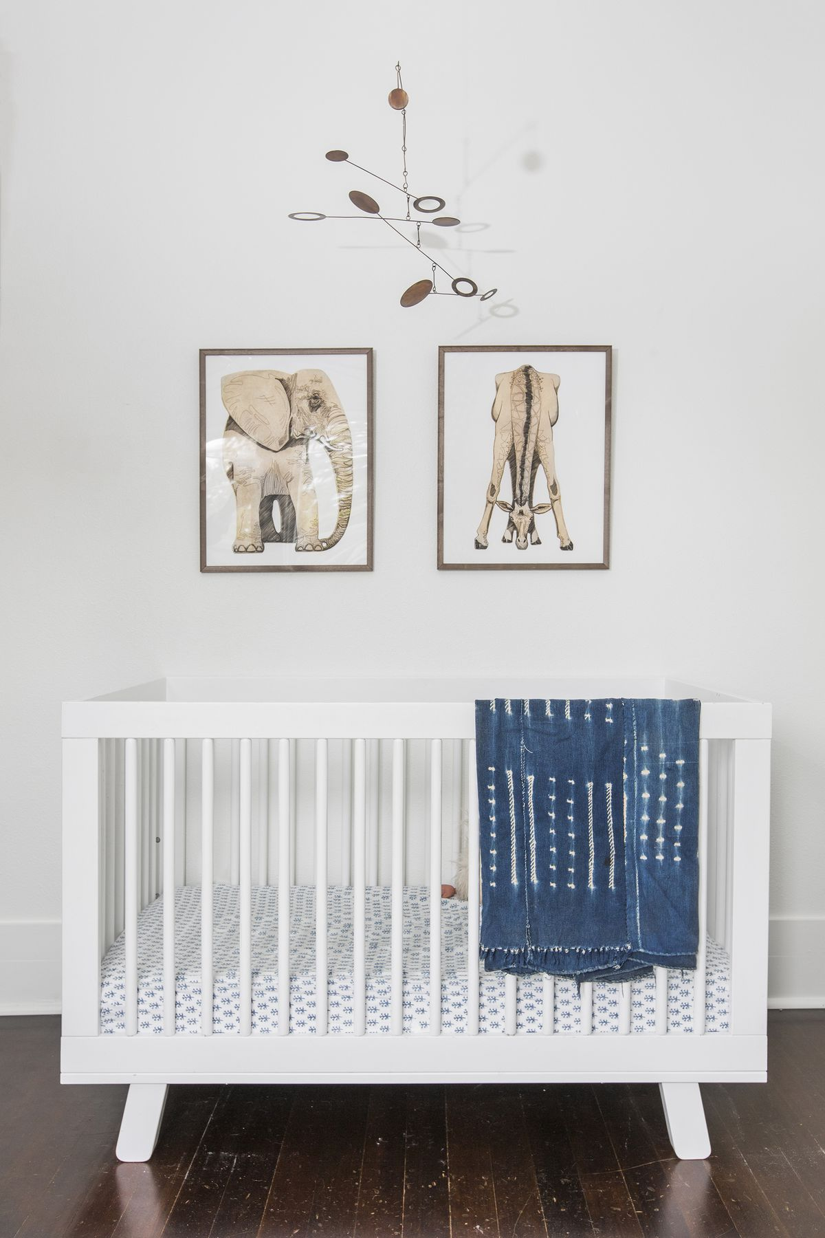 A white crib has a bronze mobile above it, as well as a print of an elephant and a giraffe.