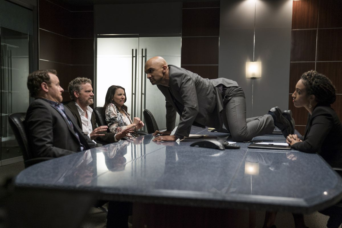 """Usman Ally (on table) plays a hot-tempered studio exec on """"Nobodies."""" 
