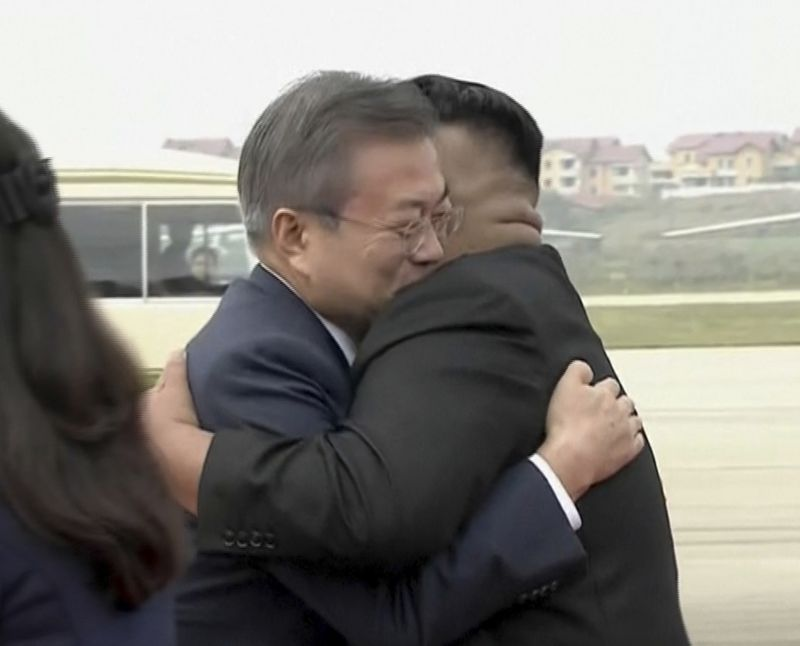 North Korean leader Kim Jong Un and South Korean President Moon Jae-in hug on the tarmac at Pyongyang's airport on on September 18, 2018.