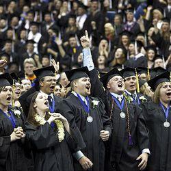 Utah State University graduates sing during commencement ceremonies at the Spectrum on Saturday.