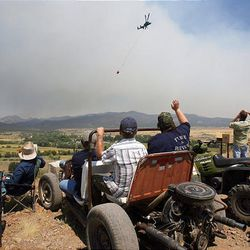 New Harmony residents gather to watch the fire and wave at passing helicopters on Sunday. Eleven structures burned over the weekend, but no injuries have been reported.