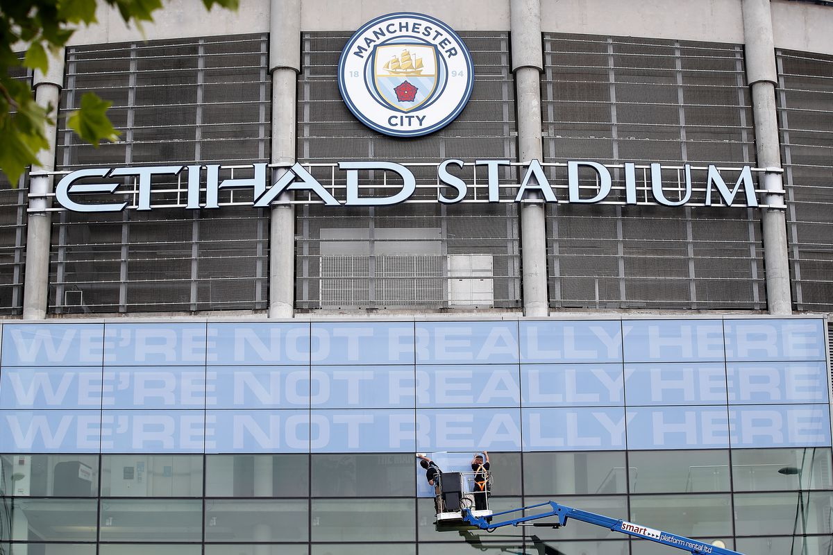 Workmen place signs at main entrance to the Etihad Stadium, home of Manchester City. The Premier League restarts tomorrow night with Aston Villa v Sheffield United and Manchester City v Arsenal.