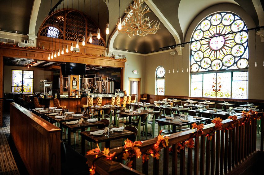 A church-like dining room with stained glass windows and an antler chandelier.