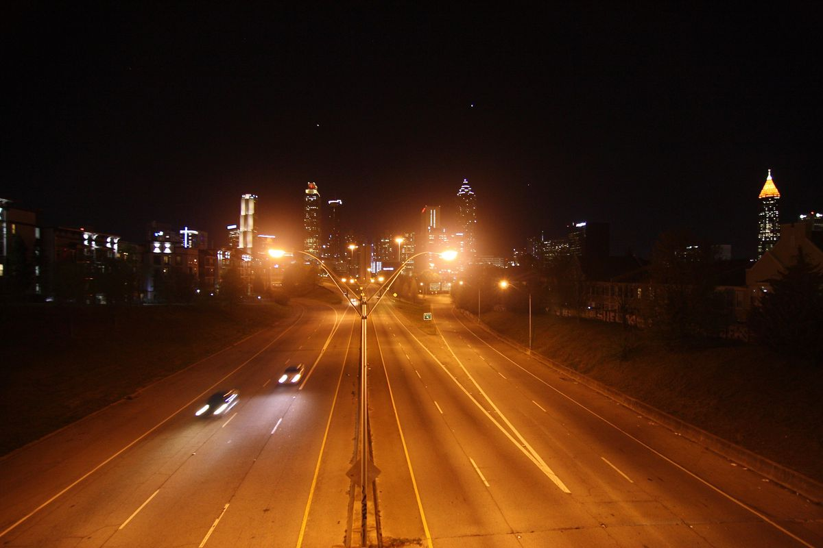 An empty city street with a skyline in the background and many streetlights in the middle.