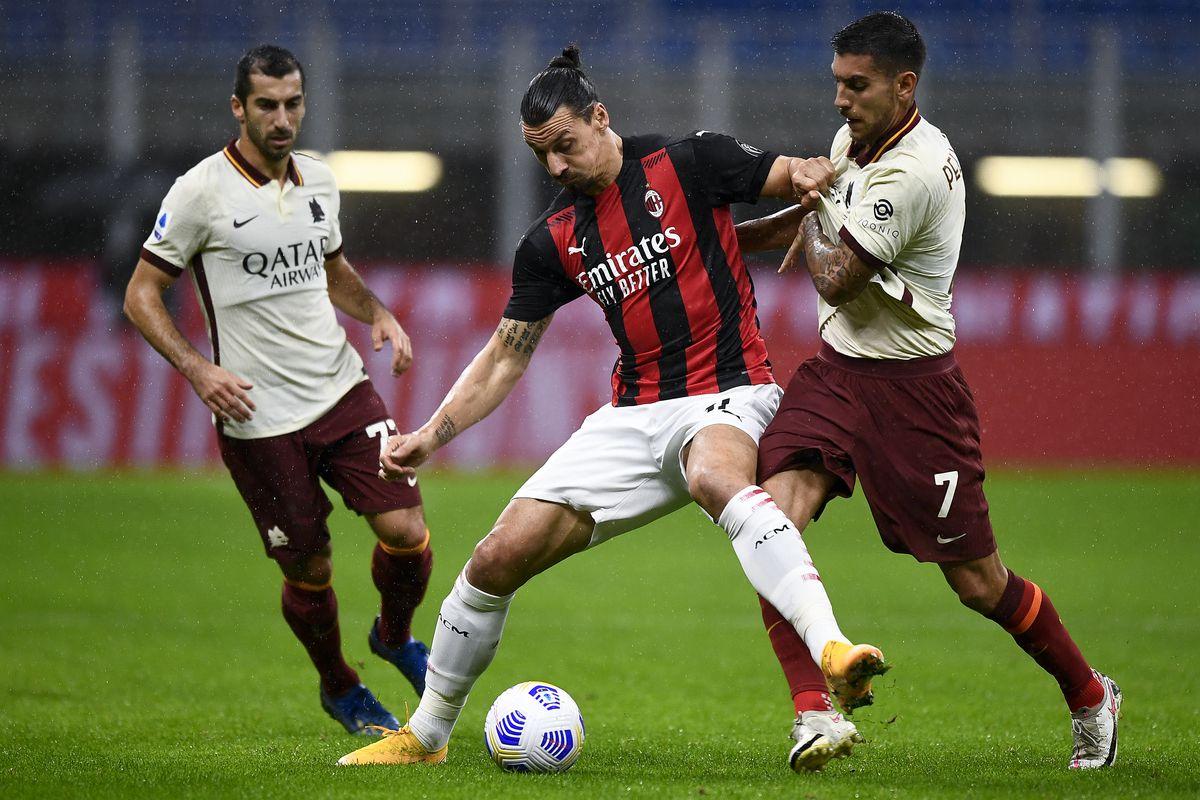 Zlatan Ibrahimovic (C) of AC Milan is challenged by Lorenzo...