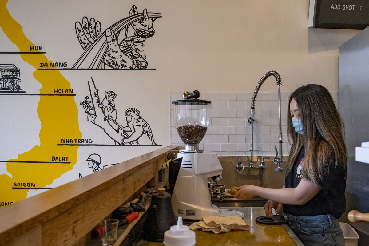 A woman wearing a mask fills an espresso portafilter with beans ground from a machine.