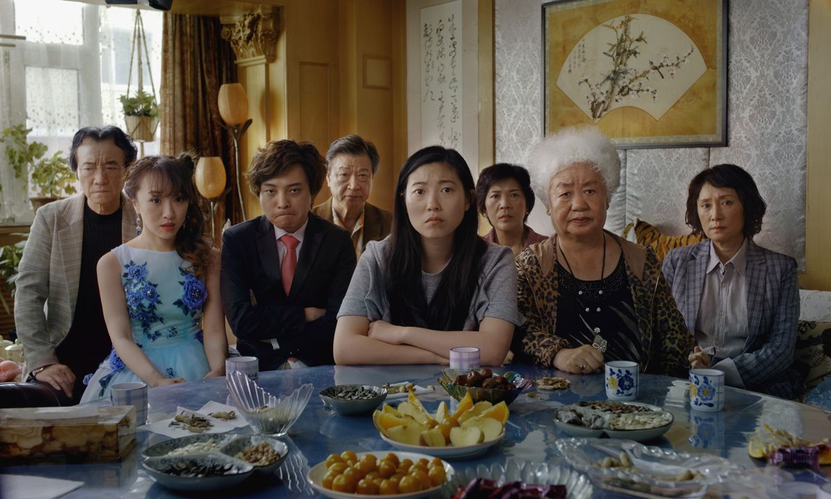The family gathered around a table, with Billi (Awkwafina) at the center and Little Nai Nai (Hong Lu) to her left.