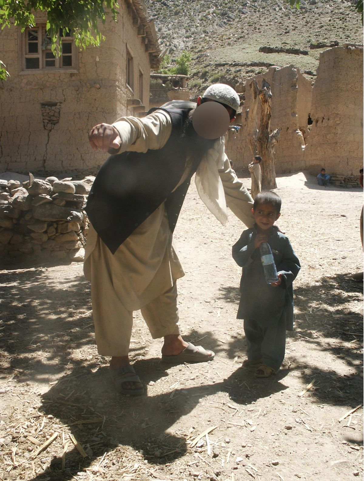 Taroon, a former associate of Eric Eliason, a former Utah National Guard chaplain and now a Brigham Young University professor, helps a child look for his soccer ball in an Afghan village near the Pakistani border during Eliason's deployment in 2004. Taroon was murdered by the Taliban in the late-2000s, and now Eliason and several former military friends are working to help Taroon's wife, daughter, two sons and brother escape Afghanistan.