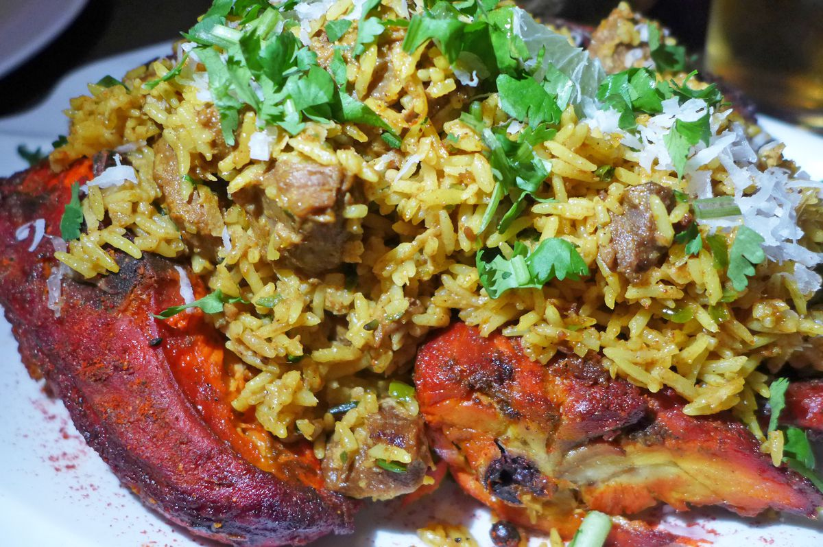 A very red chicken is stuffed with biryani.