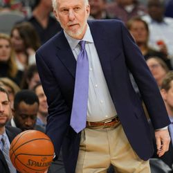 San Antonio Spurs head coach Gregg Popovich returns the ball to a referee during the first half of an NBA basketball game against the Utah Jazz, Saturday, Feb. 3, 2018, in San Antonio. (AP Photo/Darren Abate)