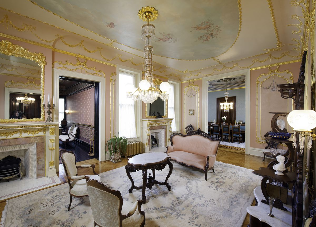 A pink and cream formal sitting area features gold trim and painted ceilings, a large chandelier, and formal fireplace.