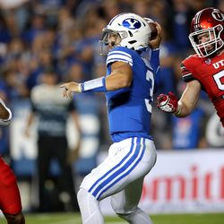 Utah Utes safety Brandon McKinney (28) and Utah Utes linebacker Hayden Furey (54) try to get to Brigham Young Cougars quarterback Jaren Hall (3) as BYU and Utah play an NCAA football game at LaVell Edwards Stadium in Provo on Saturday, Sept. 11, 2021. BYU won 26-17, ending a nine-game losing streak to the Utes.