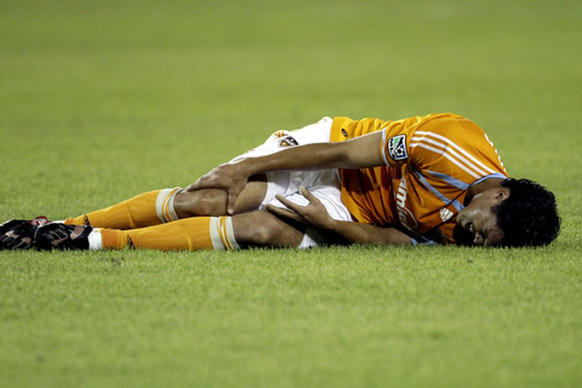 HOUSTON - MAY 05:  Luis Landin #7 of the Houston Dynamo lays on the field in pain after taking a hard hit during a game with FC Dallas at Robertson Stadium on May 5, 2010 in Houston, Texas.  (Photo by Bob Levey/Getty Images)