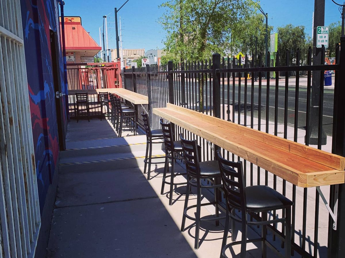A patio with high-top seats looking at a fence.