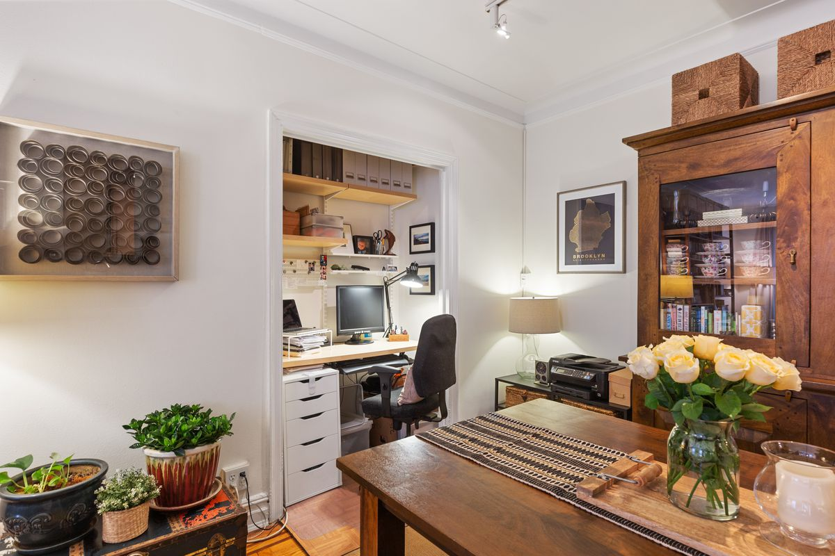 A nook with crown moldings, a desk with a computer, white walls, and wooden furniture.