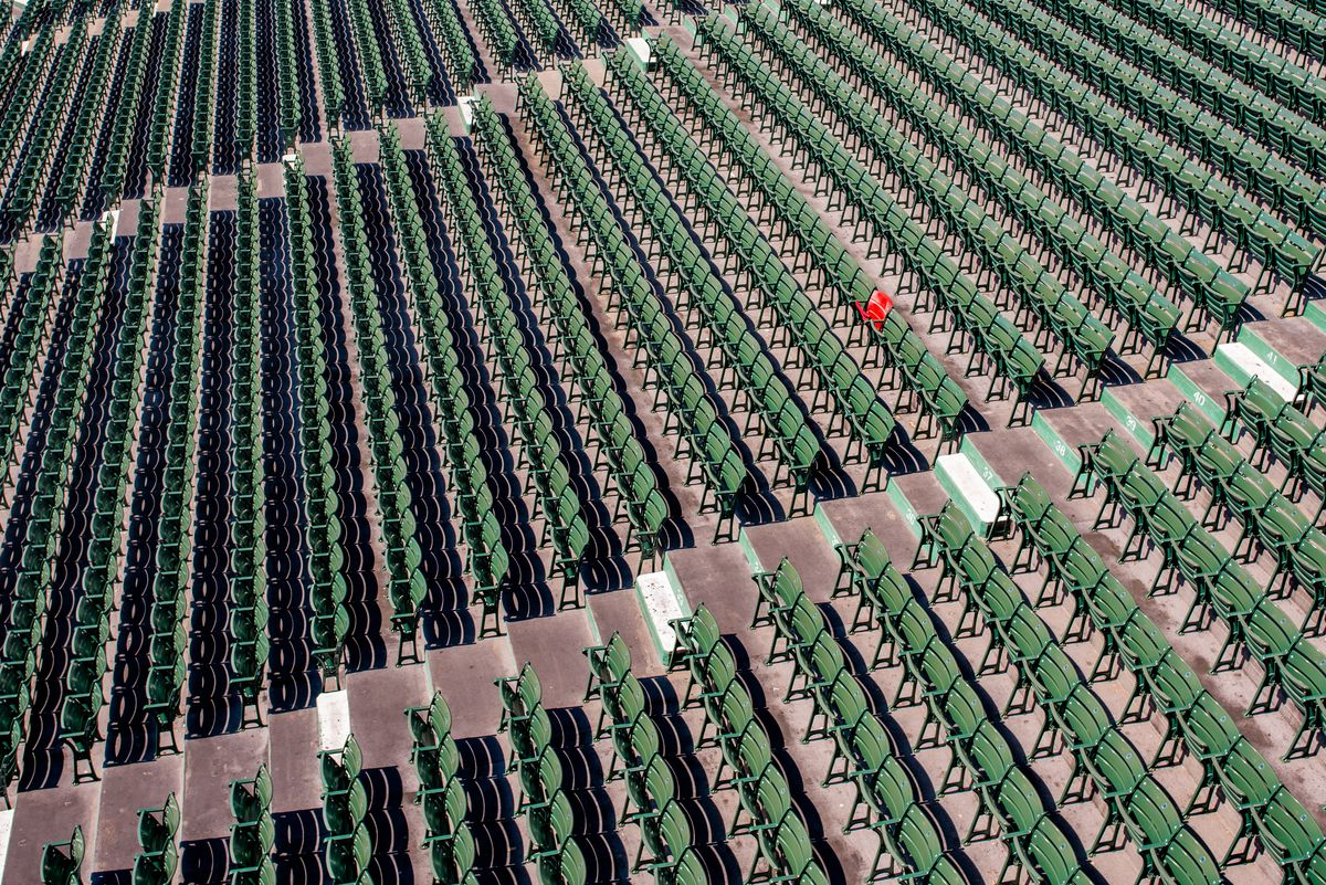 A lone red seat among several rows of green seats.