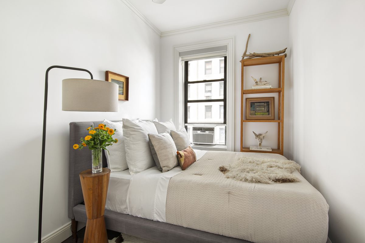 A small bedroom with a window, base moldings, and a queen-size bed.
