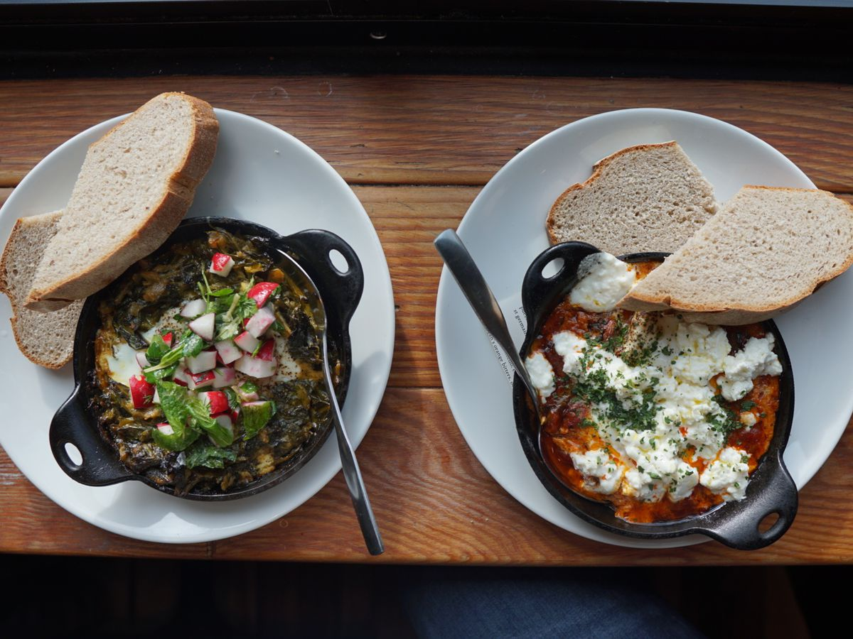 Two white plates sit next to each other with individual cast irons filled with red and green shakshukas. Both bowls come with two slices of bread