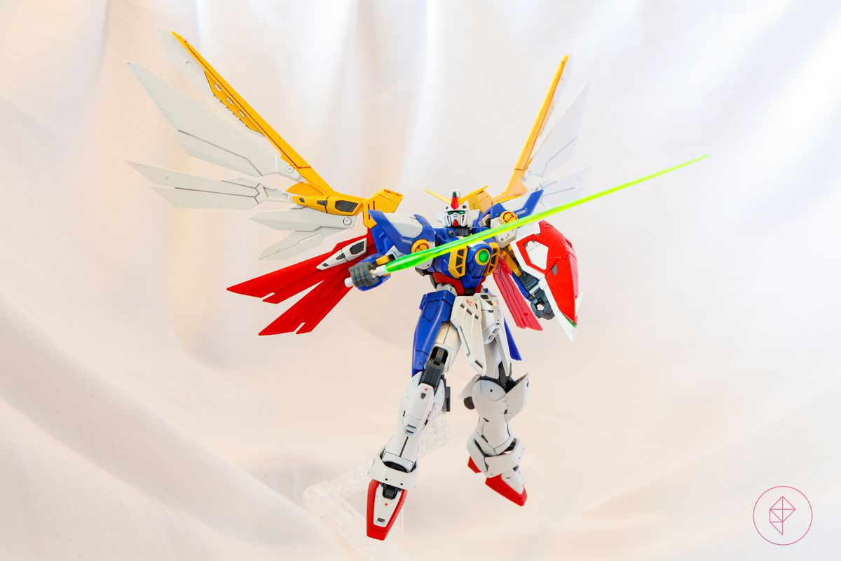 The Wing Gundam Gunpla kit floats in the air, supported by a clear plastic stand.