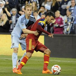 Real Salt Lake's Javier Morales shields Sporting KC's Seth Sinovic from the ball during a game at Sporting Park in Kansas City, Kan., on Saturday, April 5, 2014.