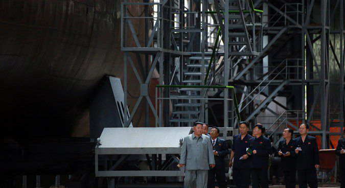 Kim Jong Un joined by nuclear officials near what appears like a nuclear-capable submarine.