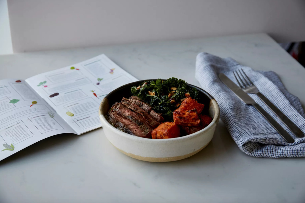 A plate of food including orange sweet potatoes, green kale, and an open menu placed in front of it