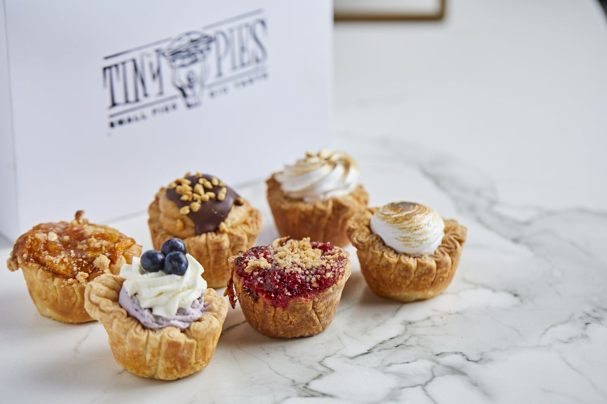 Six miniature pies with cream toppings and fruits and crumbles.