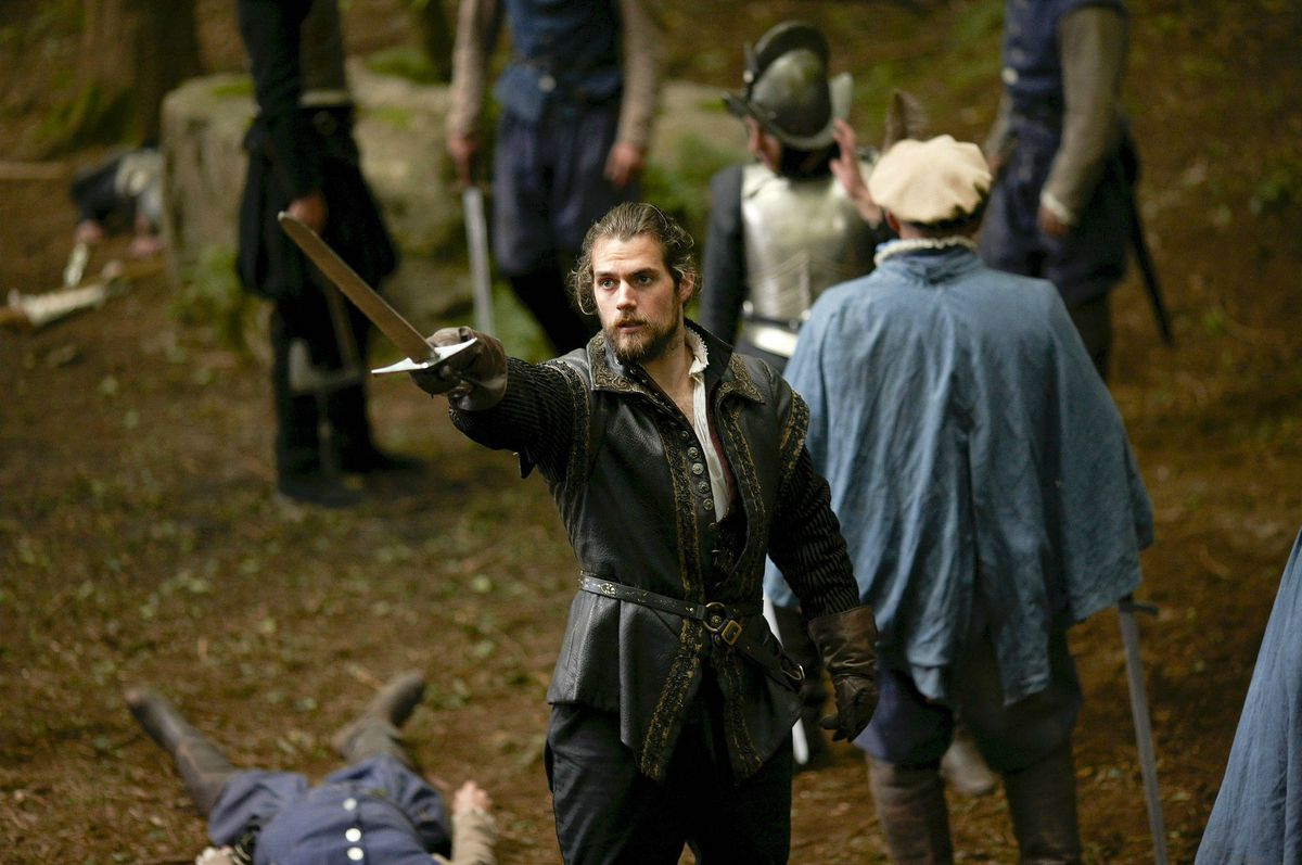 Charles Brandon (Henry Cavill) holds up a sword in a screenshot from The Tudors
