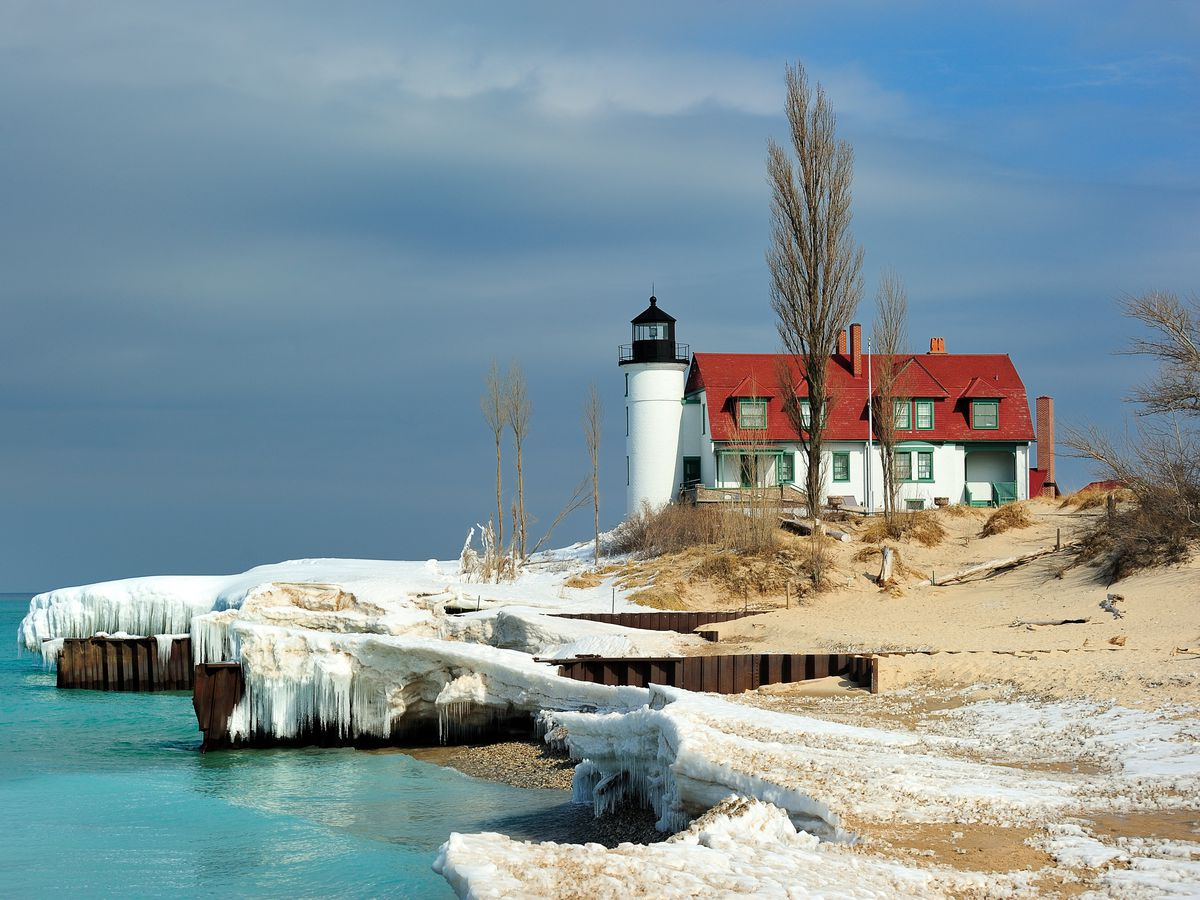 A lighthouse and barn next to a lake with an icy shore.