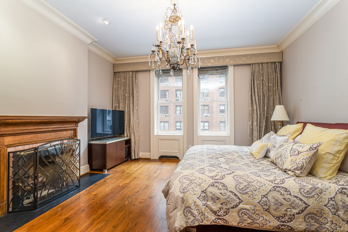 A bedroom with hardwood floors, a chandelier, a large bed, and a fireplace.