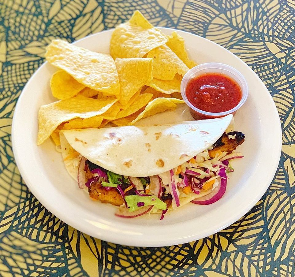 A taco with slaw, tortilla chips, and salsa