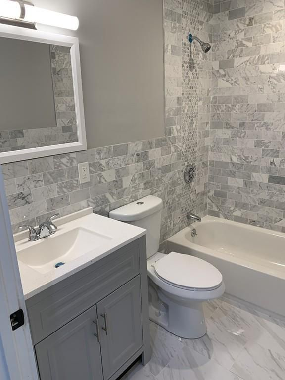 A new bathroom with no curtain on the shower.