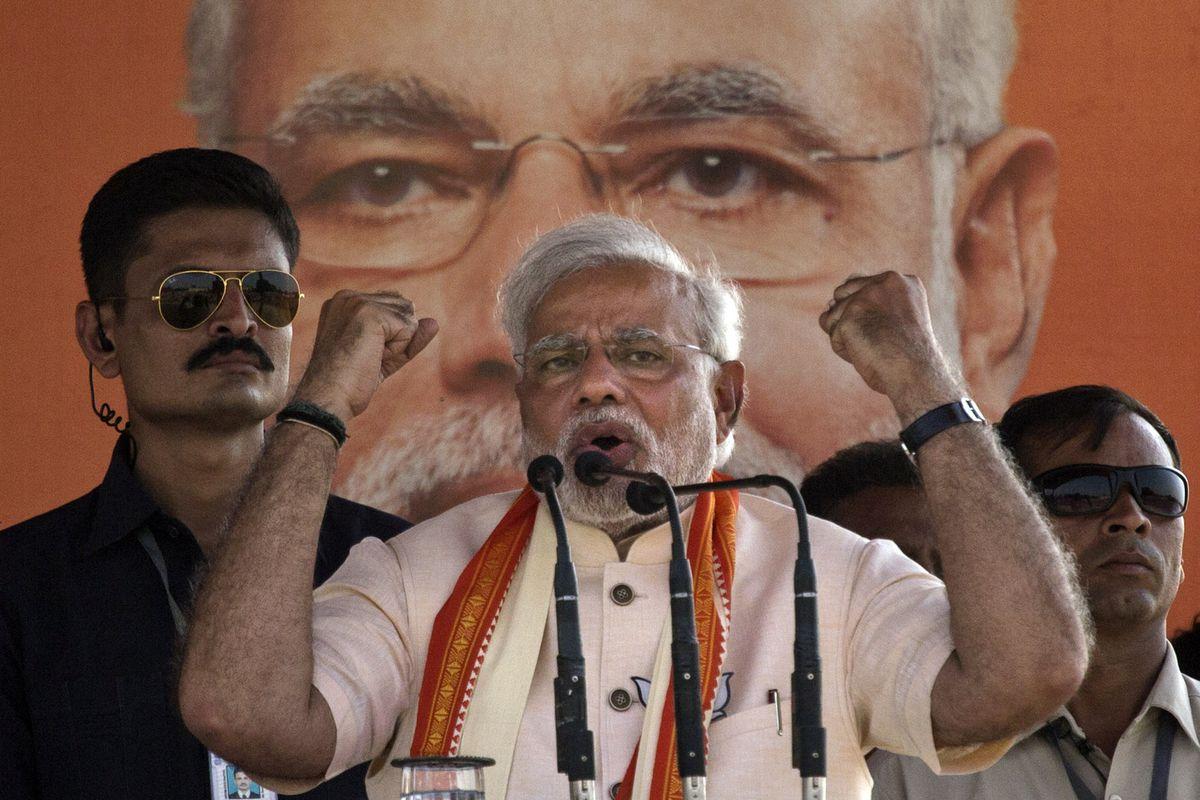 Narendra Modi speaking in front of a giant poster of Narendra Modi