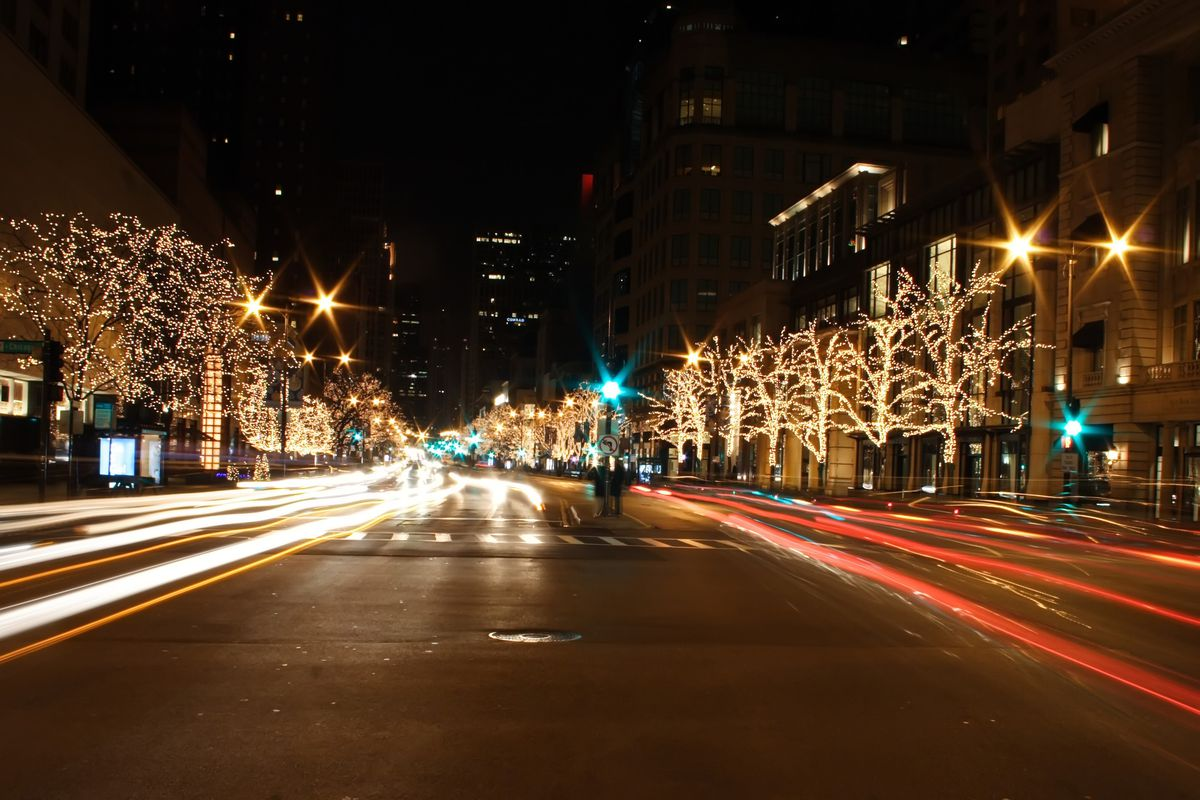 A shot from the center of a street with blurred car lights, lighted trees and street lamps.