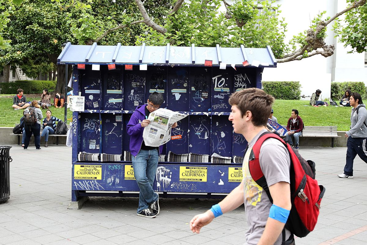 A student reads a copy of the student newspaper at UC Berkeley's Sproul Plaza.