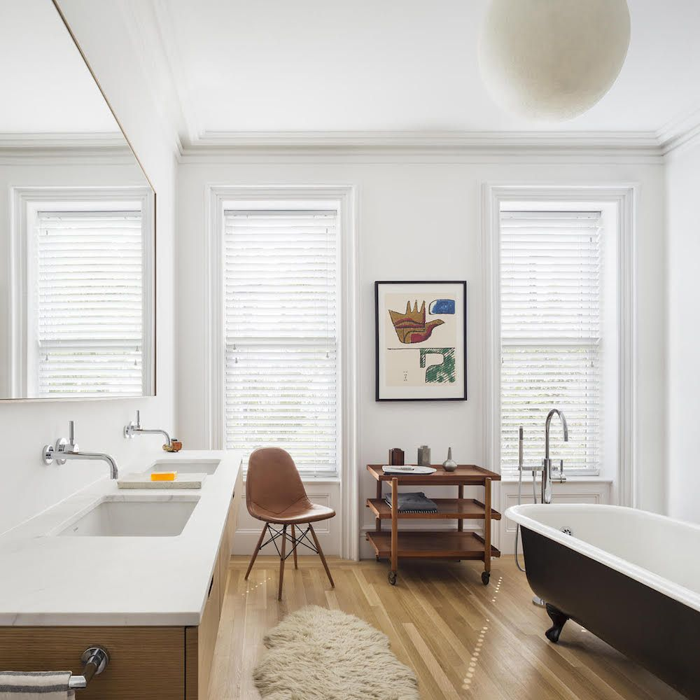 The master bathroom, with cabinetry also by Achenbach. The restored clawfoot tub that was original to the brownstone was painted in Sherwin Williams Tricorn Black. The teak tea cart by Poul Hundevad was thrown in as part of a deal at an estate sale.