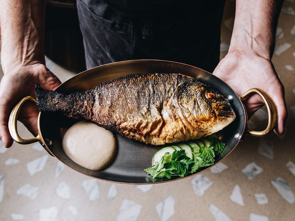 A full grilled fish on a platter with cucumbers, being held by two hands and shot from above.