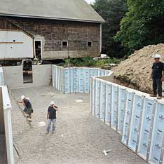 <p>A crew from Superior Walls installs the foundation — panels of insulated concrete that are set on a bed of crushed stone, adhered to each other with a urethane adhesive, and then bolted together. The entire foundation was built in a day, no curing time needed.</p>