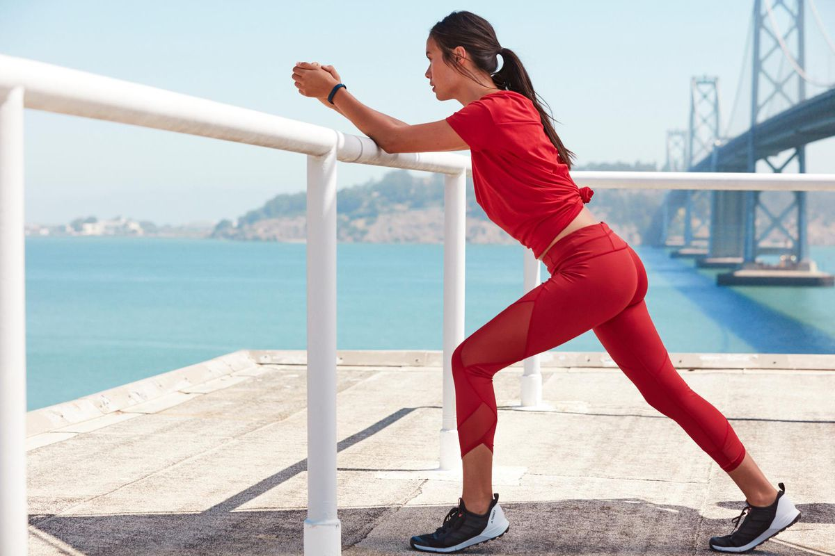 A woman in red workout clothes and sneakers, stretching