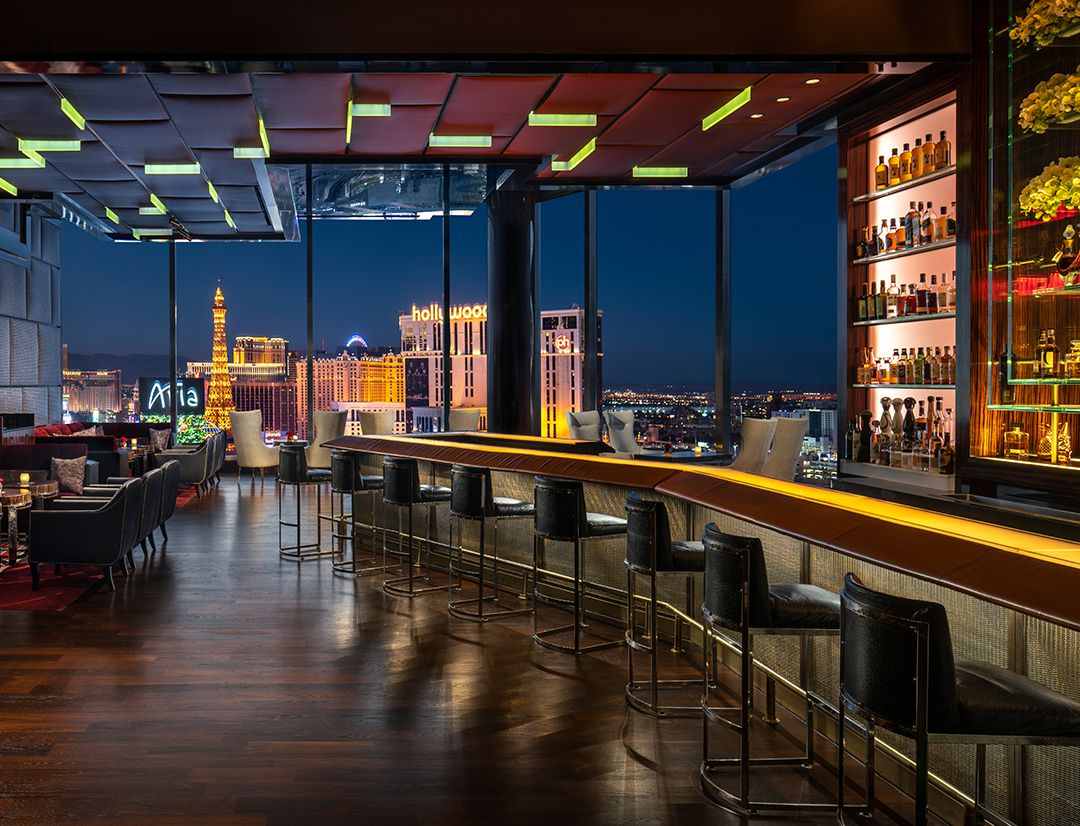 A bar with a dramatic skyline at night seen through floor-to-ceiling windows